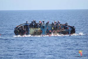 """Migrants are seen on a capsizing boat before a rescue operation by Italian navy ships """"Bettica"""" and """"Bergamini"""" off the coast of Libya in this handout picture released by the Italian Marina Militare on May 25, 2016. Marina Militare/Handout via REUTERS    ATTENTION EDITORS - THIS PICTURE WAS PROVIDED BY A THIRD PARTY. FOR EDITORIAL USE ONLY."""